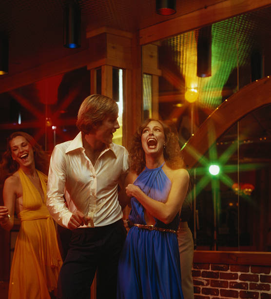 Couples dancing together at nightclub, smiling