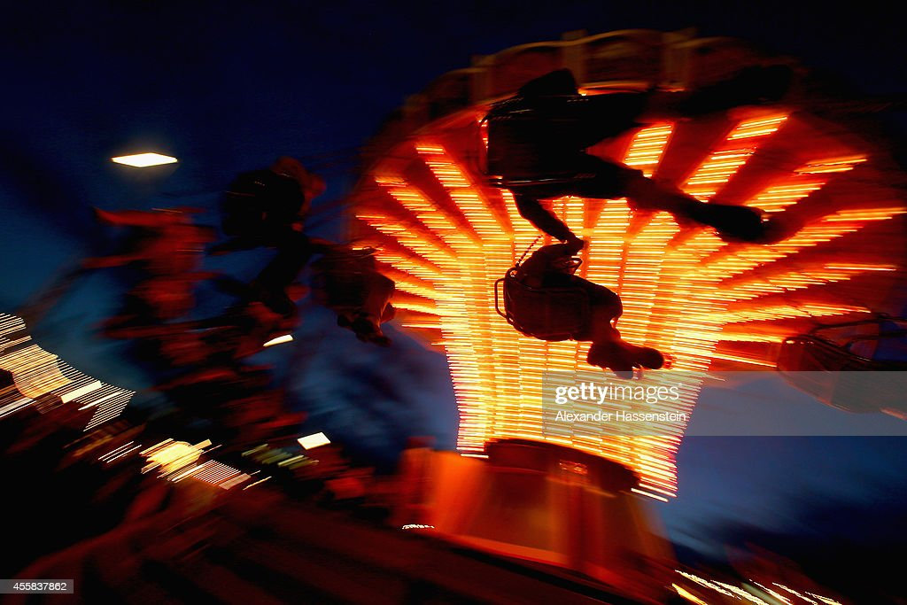Couples dressed in traditional Bavarian clothing Dirndl and Lederhosen holding their hands whilst riding on a merry-go-round on the first evening of the opening day of the 2014 Oktoberfest at Theresienwiese on September 20, 2014 in Munich, Germany. The 181st Oktoberfest will be open to the public from September 20 through October 5 and traditionally draws millions of visitors from across the globe in the world's largest beer fest.