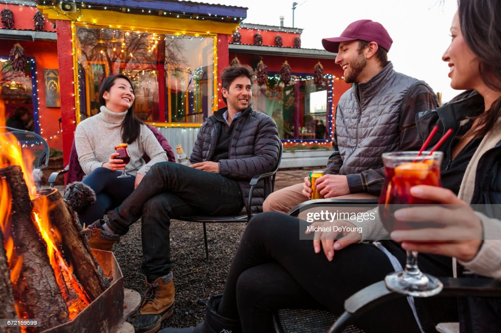Couples drinking cocktails and beer outdoors at storefront campfire : Stock Photo