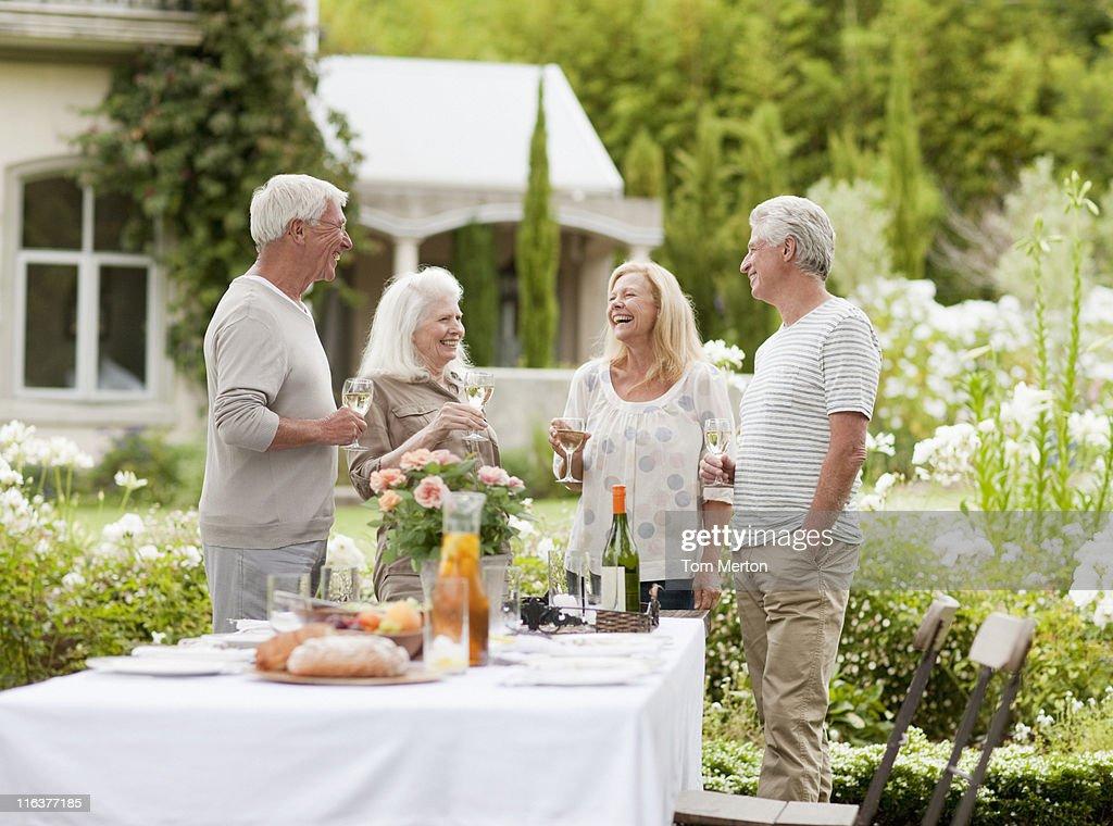 Couples drinking wine in garden : Stock Photo
