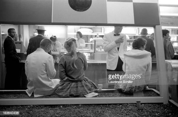 Couples eat and drink at a fastfood counter during an adultsonly night at the Disneyland theme park Anaheim California early 1960s On Friday and...