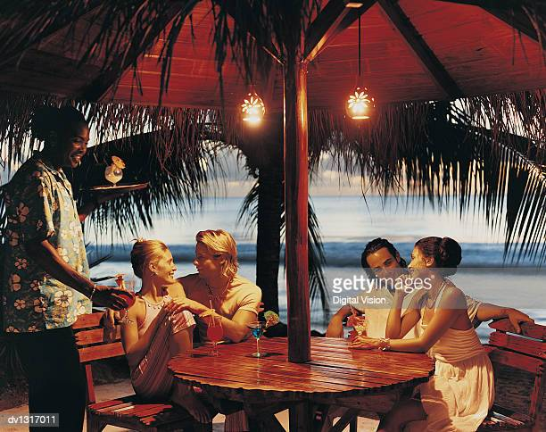 Couples Enjoying Cocktails in a Bar on the Coast at Twilight