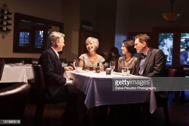 couples enjoying dinner in restaurant together - four people stock-fotos und bilder