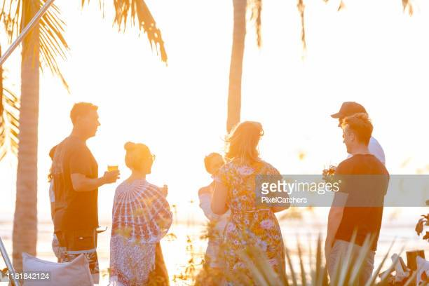 couples enjoying island sunset beach party - image title stock pictures, royalty-free photos & images