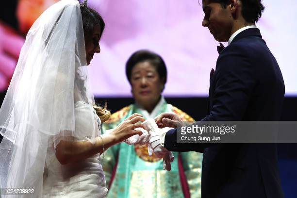 Couples exchange their wedding rings in a mass wedding ceremony held by the Family Federation for World Peace and Unification aka Unification Church...