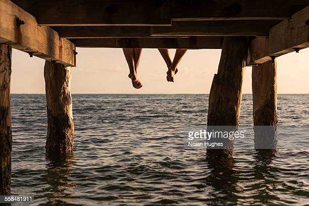 couple's feet dangle from end of pier - pier stock pictures, royalty-free photos & images