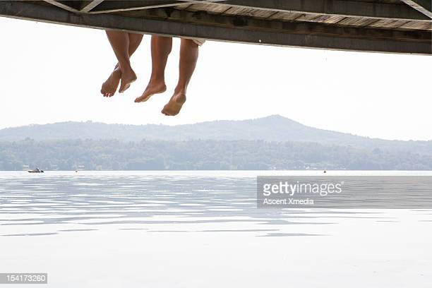 Couples' feet dangle from wooden wharf, above lake