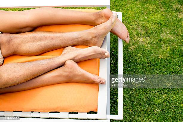 A couple's feet entwined on a sunlounger