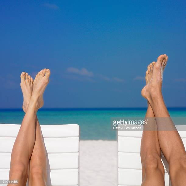 Couple's feet on beach chairs