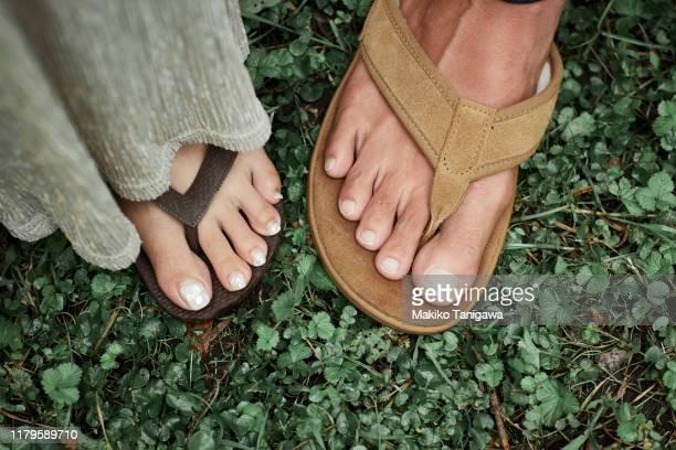 couple's feet on grass - makiko tanigawa ストックフォトと画像