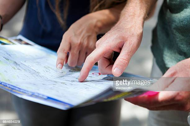 Couples hands pointing on city map
