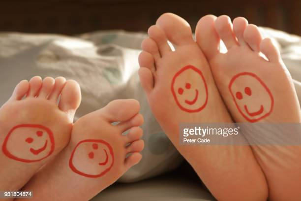 couples happy feet in bed - human foot stock pictures, royalty-free photos & images