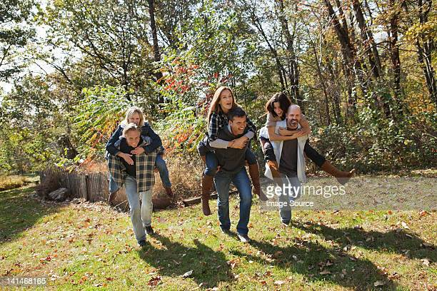Couples having a piggyback race outdoors