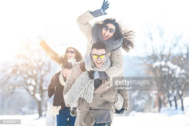 Couples having fun in piggyback ride in snow forest