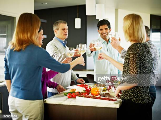 couples in home kitchen toasting wine glasses