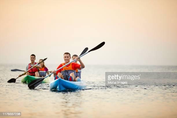 couples kayaking on river during summer sunset - kayak foto e immagini stock