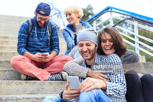 Couples laughing and using smart phone