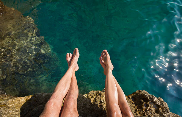 Couple's Legs Above Turquoise Ocean