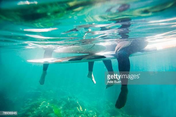 couple's legs and surfboards underwater. - unterhalb stock-fotos und bilder