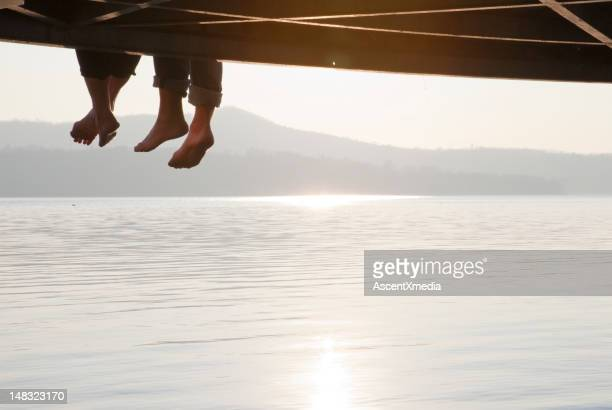 A couples' legs dangling from a wooden pier