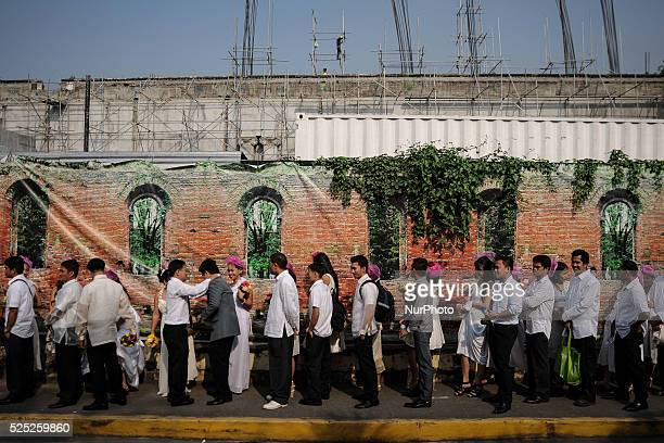Couples line up in a sidewalk during a mass wedding ceremony on Valentine's day in Manila Philippines February 14 2014 The mass wedding was attended...