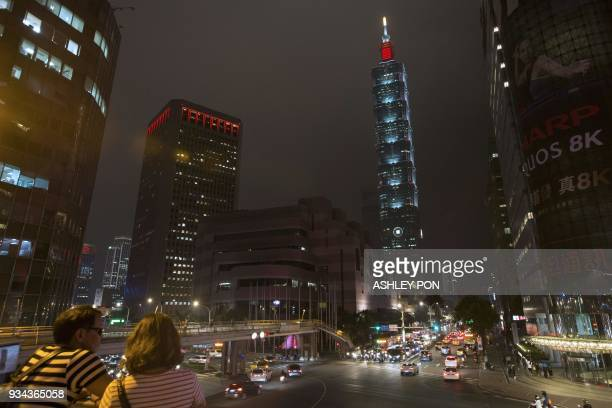 Couples look out from an overpass with the Taipei 101 building in the background in Taipei on March 19, 2018. / AFP PHOTO / ASHLEY PON