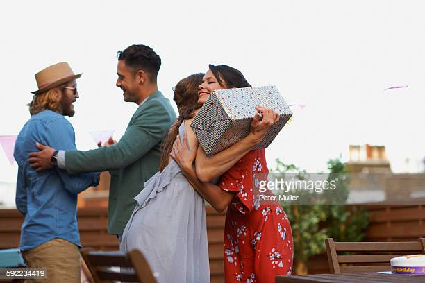 Couples meeting on roof terrace smiling, hugging holding gift