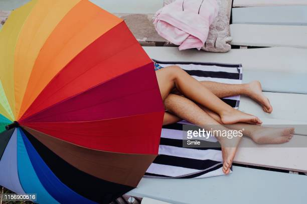 couples naked intertwined legs protruding from colourful umbrella - desire stock pictures, royalty-free photos & images