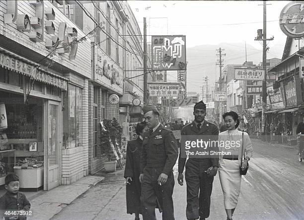 Couples of the US Army soldiers and Japanese women walk on the street circa December 1953 in Beppu Oita Japan Beppu is the one of the most popular...