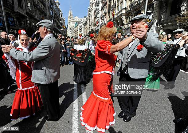 Couples perform the 'Chotis' dance as they wear typical costumes of Spain's capital Madrid known as Chulapos during a ceremony to commemorate the...