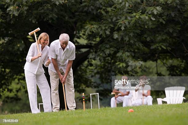 Couples playing croquet