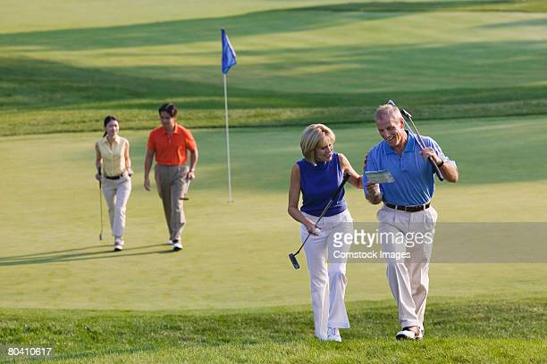 Couples playing golf