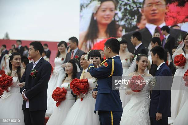 Couples pose for a group photograph during a mass wedding ceremony in Shifang, Sichuan province September 22, 2010. The ceremony was held for some 99...