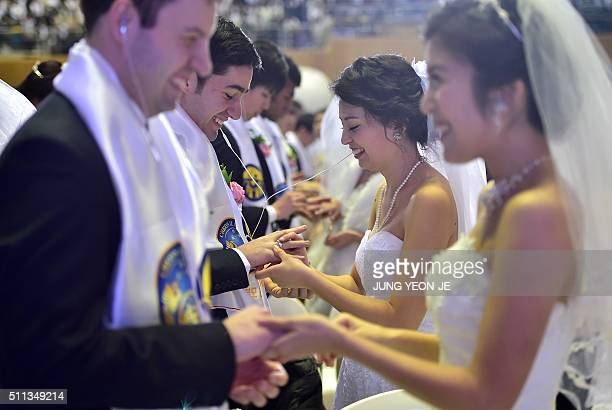 Couples put rings on the finger of their partners during a mass wedding held by the Unification Church at Cheongshim Peace World Center in Gapyeong...