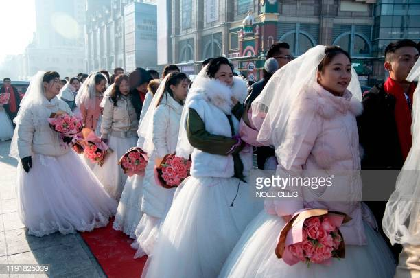 Couples queue up for a mass ice and snow wedding ahead of the opening of the Harbin International Ice and Snow Festival in Harbin in China's...