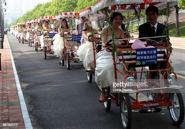 Couples ride bicycle during a lowcarbon themed group wedding ceremony at the riverside of Yangtze River on May 1 2010 in Wuhan of Hubei Province...