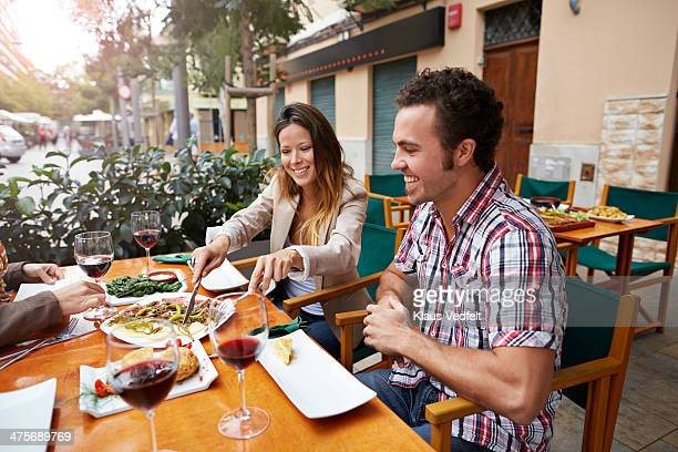 couples sharing food at restaurant - klaus vedfelt mallorca stock pictures, royalty-free photos & images