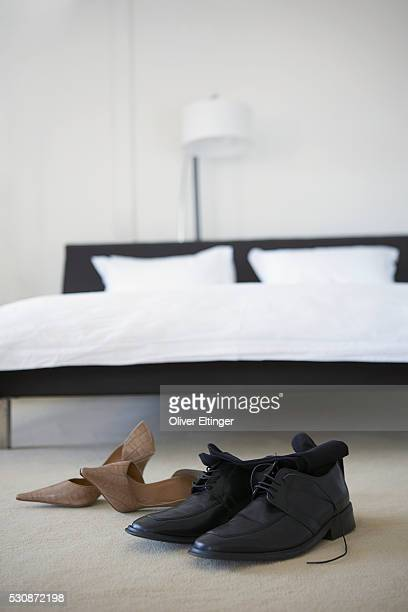 couple's shoes in bedroom - his and hers stock pictures, royalty-free photos & images