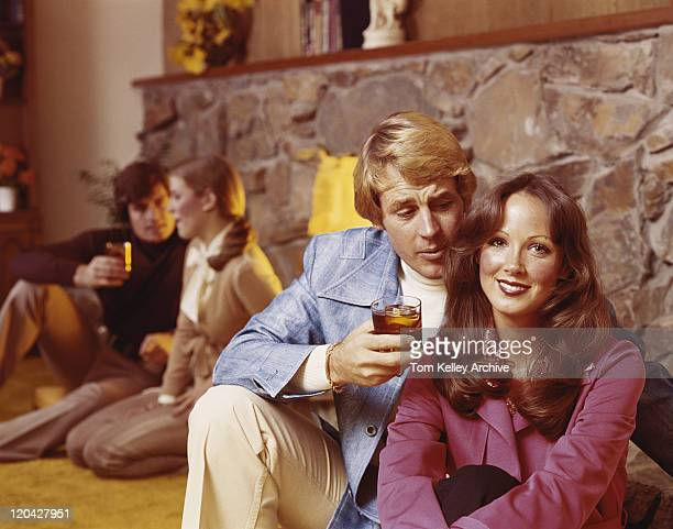 couples sitting by fireplace having drinks, smiling - 1975 stock pictures, royalty-free photos & images