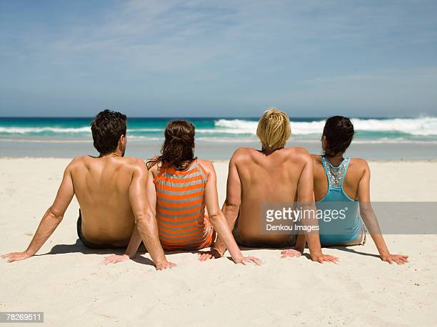 Couples sitting on the beach.
