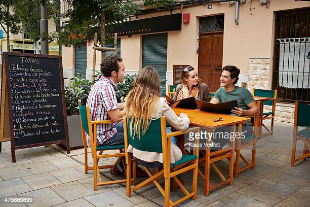 2 couples sitting with the menu at restaurant