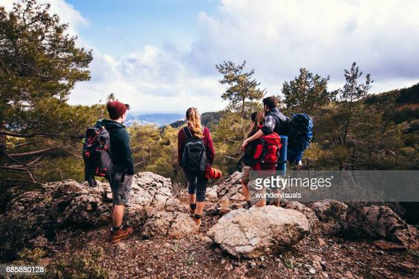 Couples standing on a mountain peak during a hiking adventure