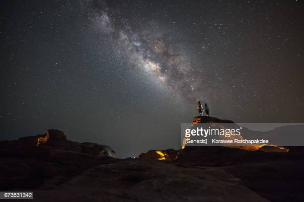 A couples standing on the rock along with a beautiful milky way in the sky