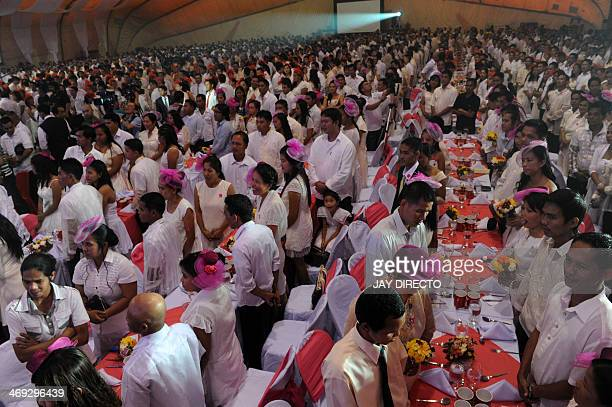 Couples take part in a free mass wedding in Manila of February 14 2014 Some 900 Couples exchanged vows inside a packed Clam shell tent on Valentine's...