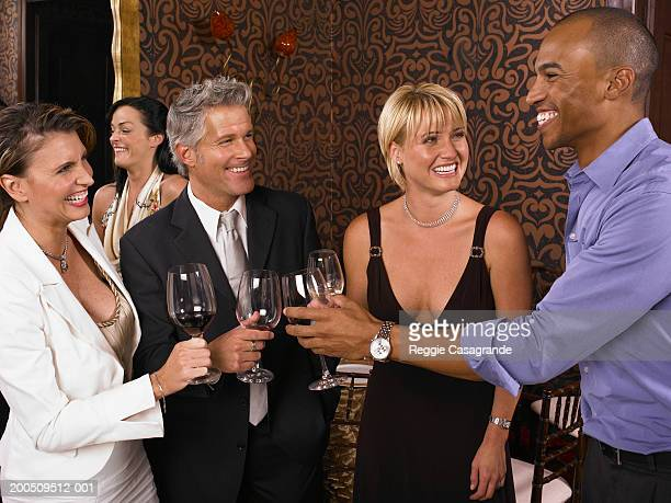 Couples toasting one another with glasses of wine