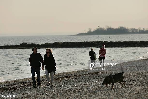 Couples walk along a beach on December 13 2015 in Westport Connecticut Temperatures across much of the New York metropolitan area continued to be...