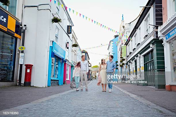 couples walking together on city street - falmouth england stock pictures, royalty-free photos & images