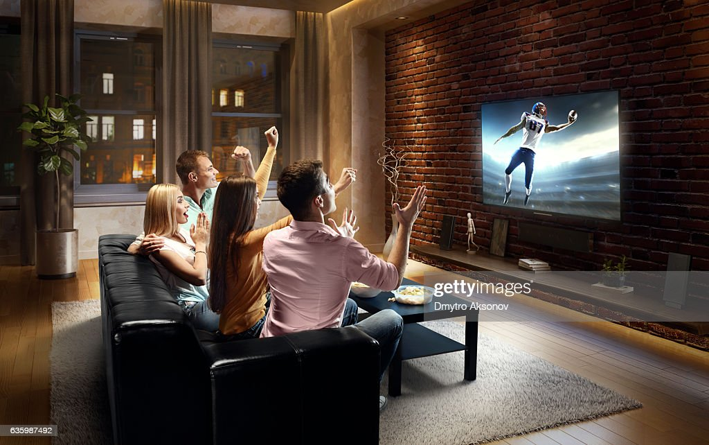 Couples watching American football game at home : Stock Photo