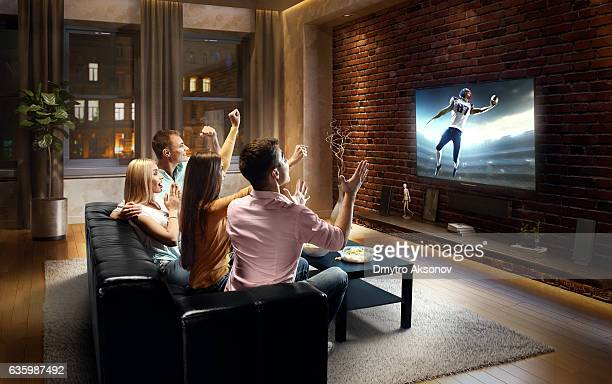 couples watching american football game at home - american football sport stock pictures, royalty-free photos & images