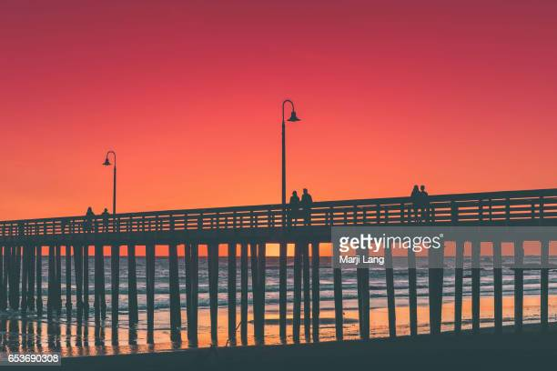 Couples watching sunset by the Pacific ocean from the Pier in Cayucos, California, USA.